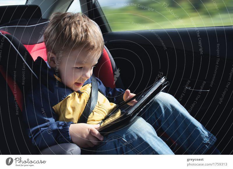 Aufgeregter kleiner Junge im Auto, der im Kindersitz sitzend mit dem Touchpad spielt Freude Glück Spielen Ferien & Urlaub & Reisen Ausflug Computer 1 Mensch