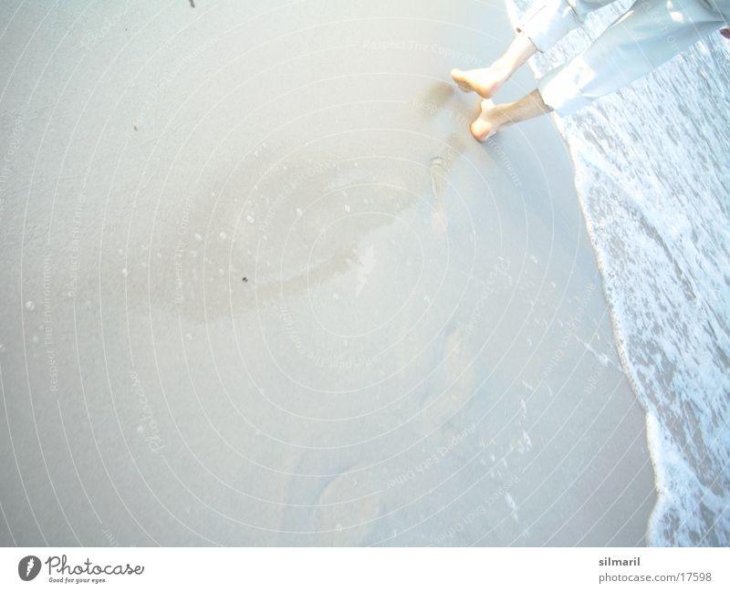 Strandserie I Mann Meer Strand Fuß Sand Beine Wellen wandern gehen laufen nass Spaziergang Hose Fußspur