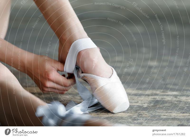 Nahaufnahme einer Ballerina beim Ausziehen der Ballettschuhe, die auf dem Boden im Studio sitzen elegant schön Studium Tanzschule Mädchen Jugendliche Fuß 1