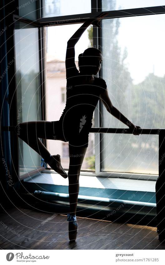 Schwarze Silhouette einer Balletttänzerin in Position an der Stange in der Nähe des Fensters Tanzen Schule Studium Mädchen Jugendliche 13-18 Jahre Tänzer