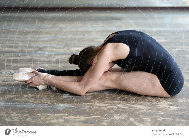 Junge Ballerina macht Dehnungsübung sitzend auf dem Boden im Studio Tanzen Schule Studium Tanzschule Mädchen Jugendliche 1 Mensch 13-18 Jahre Tänzer