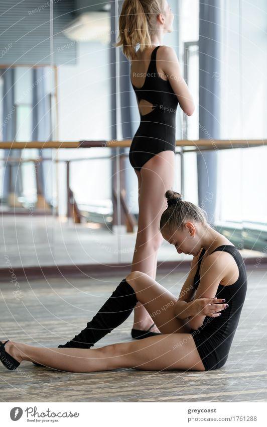 Zwei junge Ballerinen im Studio während der Pause. Eine sitzt auf dem Boden, die andere steht und schaut aus dem Fenster Spiegel Schule Studium Mädchen