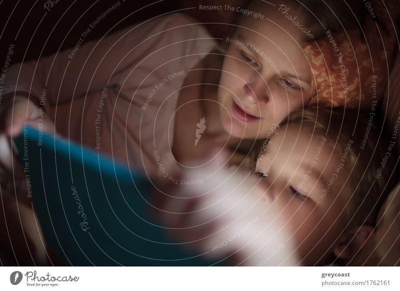 Mutter und kleiner Sohn sehen sich nachts im Bett liegend ein Video an oder spielen auf dem Touchpad Spielen Kind Computer Junge Junge Frau Jugendliche