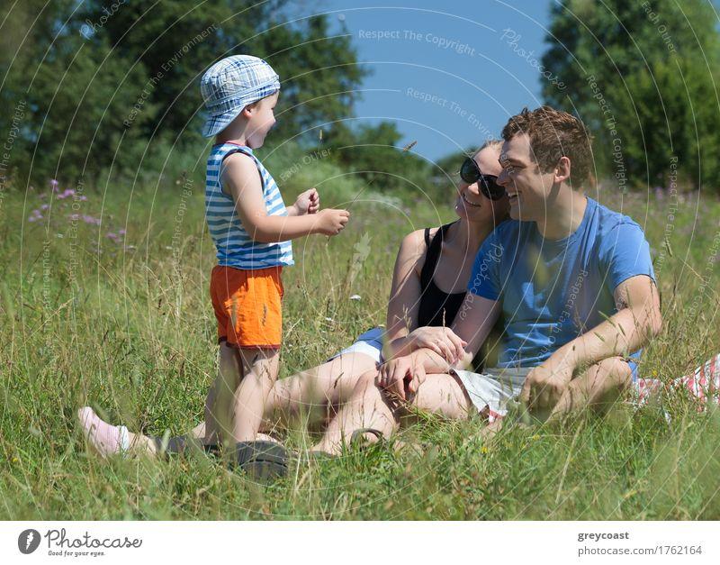 Junge Eltern und Sohn auf der Wiese an einem heißen Sommertag. Glückliches Paar sitzt auf dem Gras und schaut das Kind an. Outdoor-Familienaktivität Freude