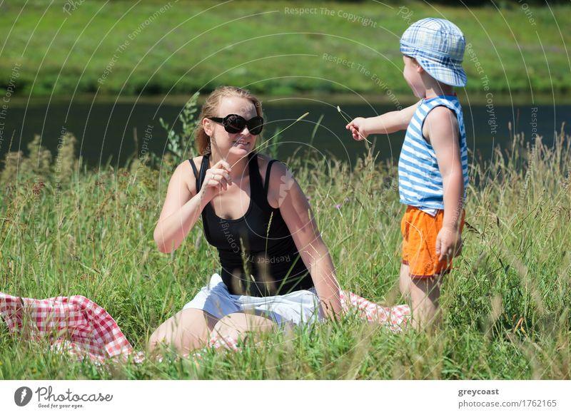 Glückliche Mutter und kleiner Sohn spielen mit Gras auf der Wiese am Ufer eines kleinen Flusses. Familie Spaß im Freien Freude Erholung Freizeit & Hobby Spielen