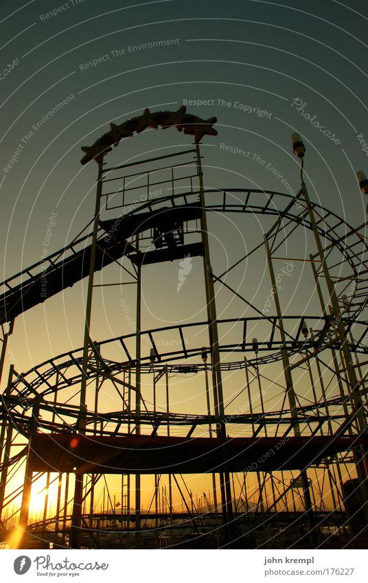 helter skelter Textfreiraum oben Dämmerung Vergnügungspark Achterbahn Fahrgeschäfte Sonnenaufgang Sonnenuntergang fahren Geschwindigkeit gelb gold rot Freude