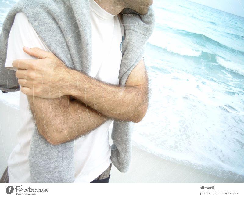 Watching the sea Mann Meer Küste warten nachdenklich frieren anonym kopflos verschränken unkenntlich gesichtslos verschränkt unerkannt Strandspaziergang In sich gekehrt Männerarm