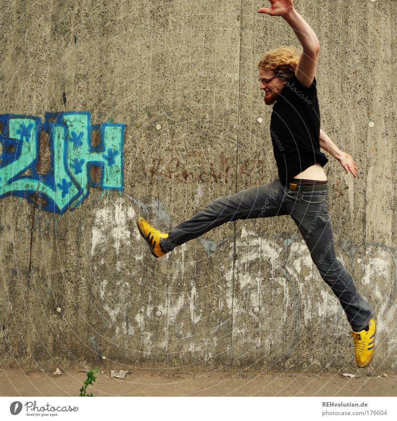 Junger Mann springt vor einer Betonwand Farbfoto Außenaufnahme Textfreiraum links Hintergrund neutral Tag Ganzkörperaufnahme Profil Blick nach vorn Stil Freude