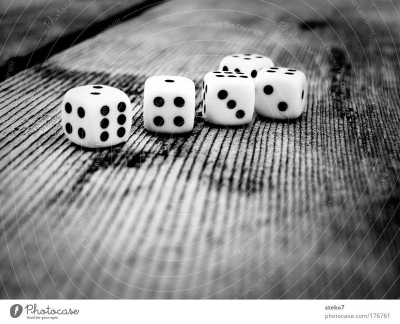 zusammengewürfelt Schwarzweißfoto Makroaufnahme Kontrast Schwache Tiefenschärfe Würfel Tisch Holz Spielen Glücksspiel Desaster würfeln Würfelspiel grau schwarz