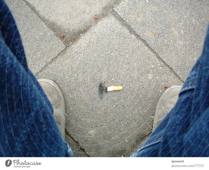 Zigarrette auf dem Boden Stein Schuhe Bodenbelag Brandasche