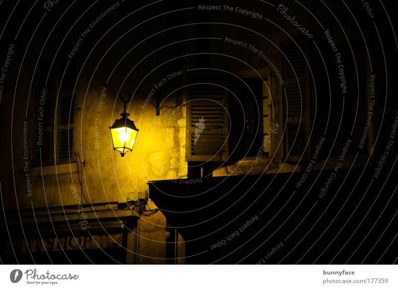 im Laternenschein Farbfoto Außenaufnahme Menschenleer Textfreiraum rechts Nacht Kunstlicht Silhouette Städtereise Stadt Altstadt Mauer Wand Fenster alt dunkel