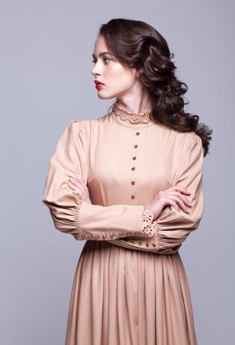 Portrait der jungen schönen Frau im Retro- beige Kleid elegant Stil Haut Gesicht Maniküre Schminke Mädchen Erwachsene Hand Mode brünett dünn retro Sauberkeit