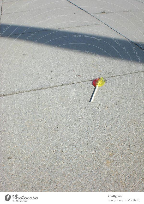 Ausgelutscht weiß rot gelb grau Lebensmittel süß liegen Süßwaren Bürgersteig verloren vergessen Lollipop Hemmungslosigkeit verschwenden wegwerfen