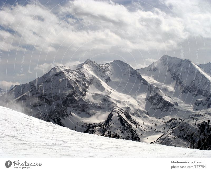 Skipiste und verschneite Berggipfel Winter Schnee Berge u. Gebirge Wintersport Wolken Alpen Schneebedeckte Gipfel hoch oben blau grau schwarz weiß Glück Idylle