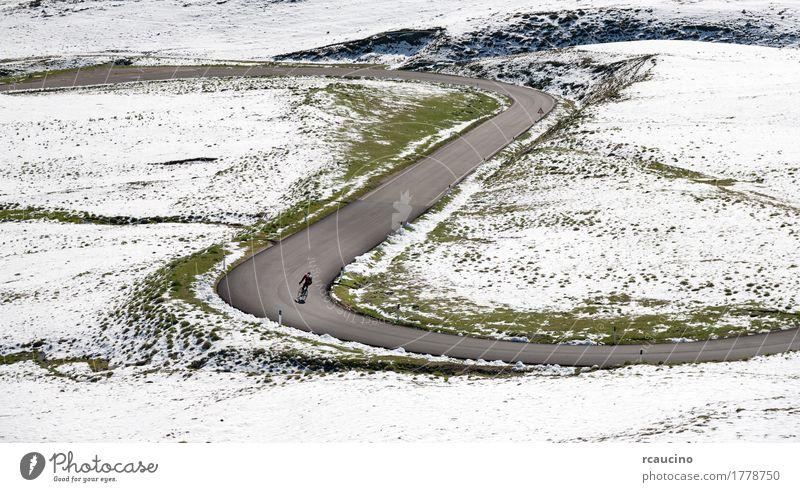 Radfahrer geht bergab entlang einer Bergstraße in einer verschneiten Landschaft schön Erholung Ferien & Urlaub & Reisen Tourismus Ausflug Sommer Winter Schnee