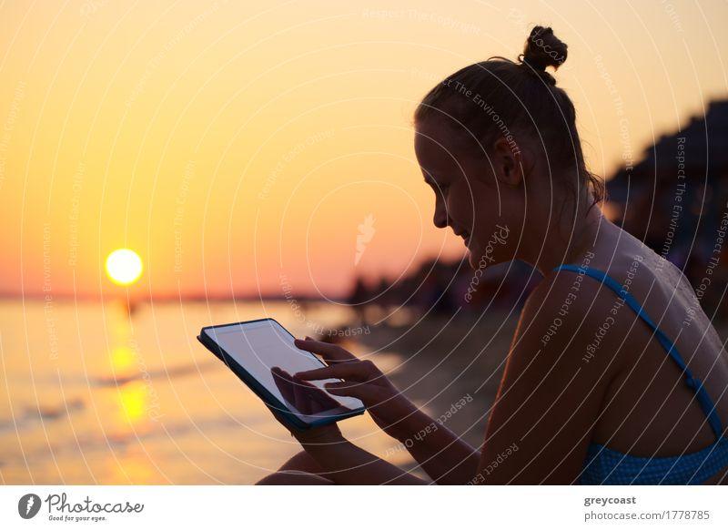 Glückliche junge Frau mit Tablet-PC am Strand bei Sonnenuntergang. Abendsonne, Meer und Strand auf dem Hintergrund Ferien & Urlaub & Reisen Sommer Computer