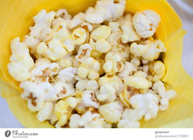 Hoher Winkel Nahaufnahme Schuss von leckeren Popcorn in gelben Papiertüte Kino Popkorn Lebensmittel Mahlzeit Tüte Snack geschmackvoll Film Hign-Winkel