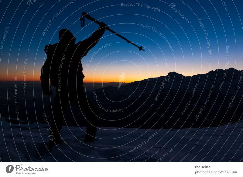 Bei Sonnenuntergang steht ein Mann auf einem schneebedeckten Gipfel und drückt seine Freude aus Mensch Himmel Natur Ferien & Urlaub & Reisen blau schön
