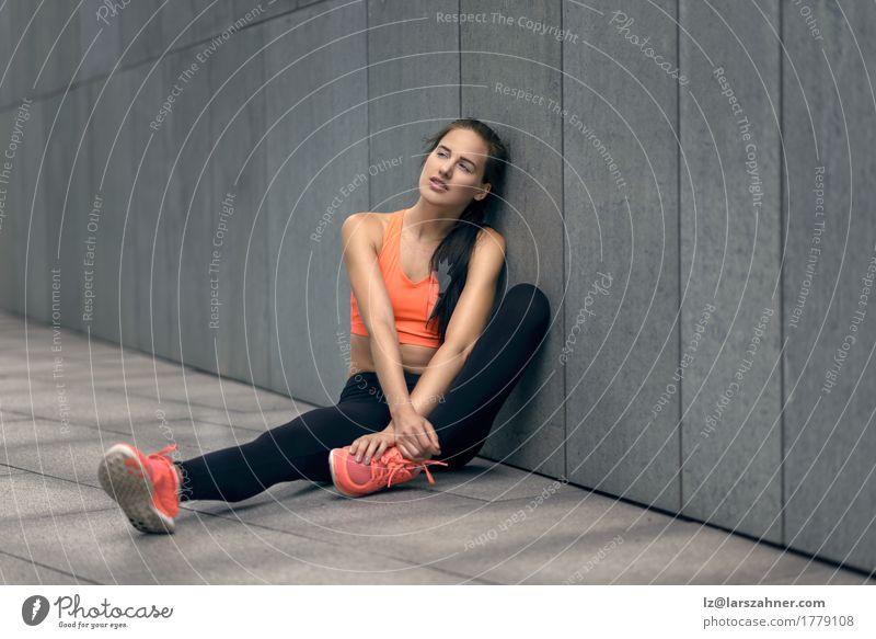 Athletische Frau, die auf der konkreten Pflasterung sitzt Zufriedenheit feminin Erwachsene 1 Mensch 18-30 Jahre Jugendliche Strumpfhose brünett Fitness sitzen
