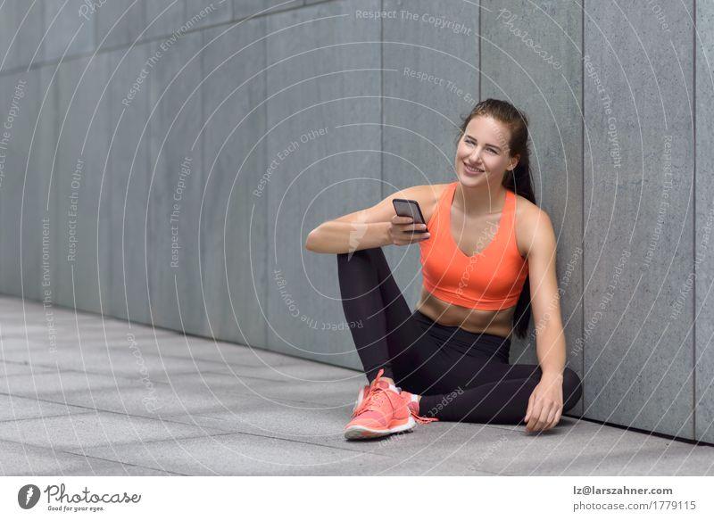 Sportliche junge Frau, die auf Vorhof mit ihrem Mobile sitzt Glück lesen PDA Erwachsene 1 Mensch 18-30 Jahre Jugendliche Strumpfhose Lächeln sitzen sportlich