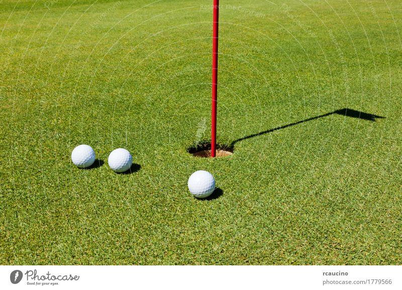 Drei Golfbälle auf dem Übungsgrün, nahe bei dem Loch Erholung Sommer Golfplatz weiß drei Ball Flugrichtung Golfball Gesunder Lebensstil Golfloch horizontal