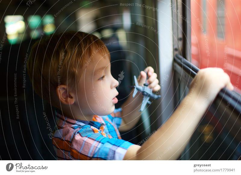 Kleiner Junge mit dem Spielzeug, das aus Zugfenster heraus schaut Ferien & Urlaub & Reisen Ausflug Kind Mensch 1 3-8 Jahre Kindheit Eisenbahn blond beobachten
