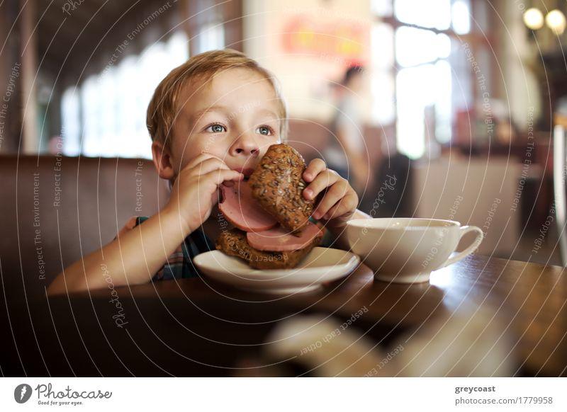Kleiner Junge in einem Cafe während des Mittagessens. Hungriges Kind isst Wurst aus seinem Sandwich Wurstwaren Brot Frühstück Abendessen Tee 1 Mensch blond