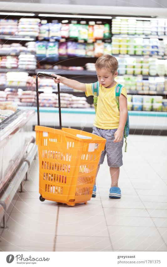 Kleiner Junge im Supermarkt schaut auf großen vollen Einkaufswagen. Kind geht allein einkaufen Mensch 1 3-8 Jahre Kindheit blond klein Einsamkeit