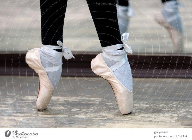 Nahaufnahme von Ballerinas Beinen in weißen Spitzen auf Holzboden in Spitzenposition. elegant Stil schön Tanzen Schule Beruf Mädchen Fuß 1 Mensch Tänzer