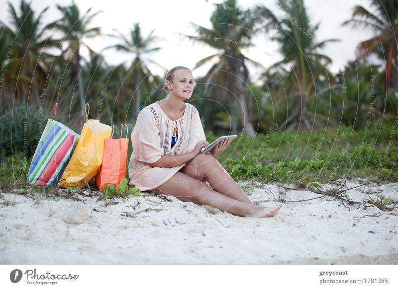 Junge lächelnde Frau mit Tablet-Computer sitzt am Strand nach gutem Einkaufen. Freizeit während des Sommerurlaubs exotisch Glück Freizeit & Hobby