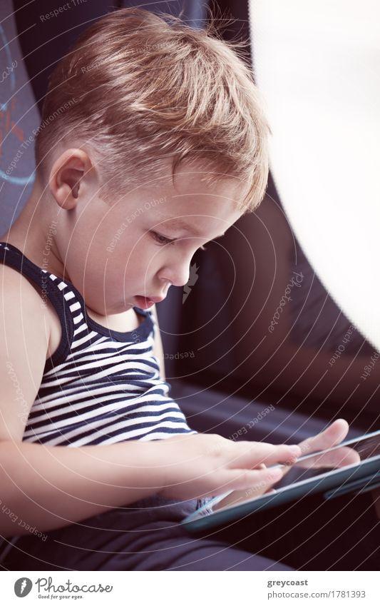 Kleiner Junge sitzt am Fenster im Bus und benutzt das Touchpad, um sich während der Fahrt zu unterhalten Freude Freizeit & Hobby Spielen