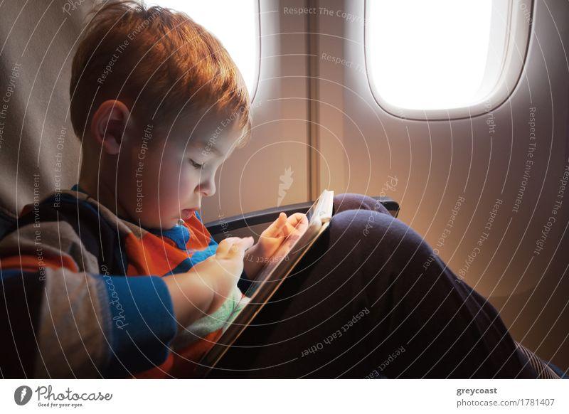Kleines Kind mit Tablet-Computer auf dem Schoß sitzen durch den Beleuchter im Flugzeug Freude Freizeit & Hobby Spielen Ferien & Urlaub & Reisen Ausflug