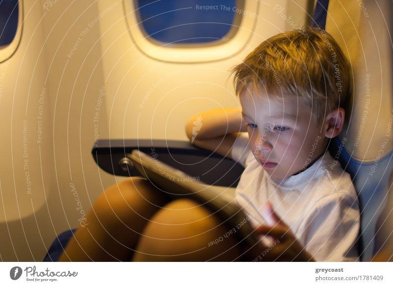 Kleiner Junge sitzt im Flugzeug und spielt auf Touchpad. Reisen mit dem Flugzeug Freude Freizeit & Hobby Spielen Ferien & Urlaub & Reisen Ausflug Kind Computer