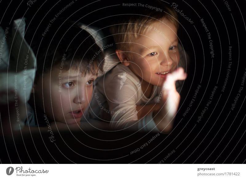 Zwei Jungen auf dem Bett liegend unter der Decke in der Nacht. Sie beobachten Film oder Cartoon auf Pad. Bildschirm erhellt ihre Gesichter in der Dunkelheit