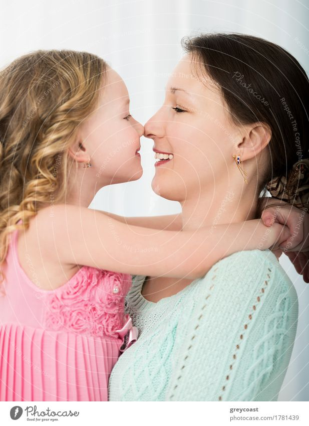 Schöne Mutter und Tochter, die sich gegenseitig mit ihren Nasen berühren. Schönes Familienporträt Freude Glück Spielen Kind Mensch Mädchen Junge Frau