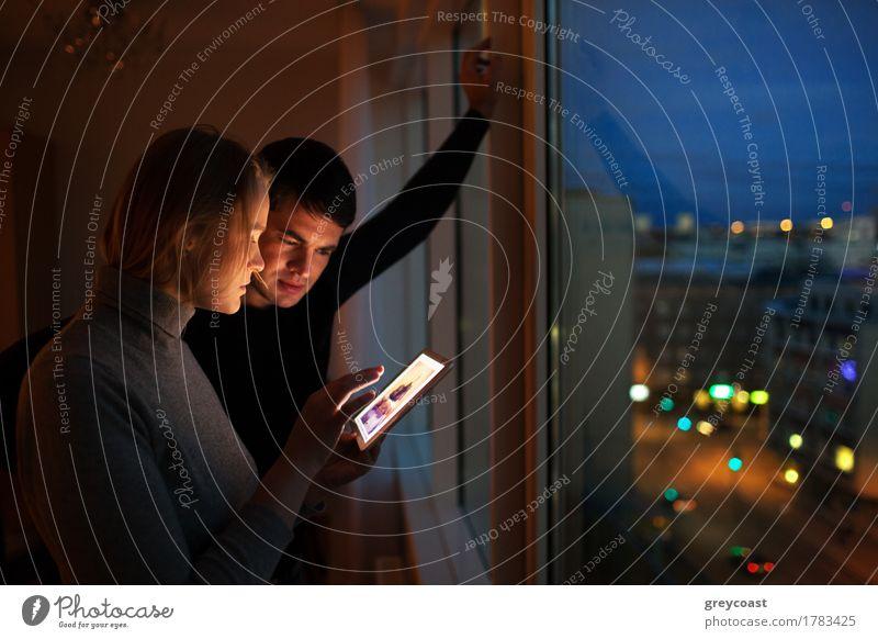Junge Leute, die zu Hause einen Tablet-Computer benutzen. Sie schauen sich Bilder am Fenster stehend am Abend an. Stadt Lichter im Freien Freizeit & Hobby