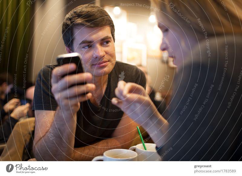 Mann, der Handy während des Treffens mit Mädchen im Café verwendet Mensch Jugendliche Junge Frau Junger Mann Erwachsene blond Lächeln Telefon Sitzung Tee