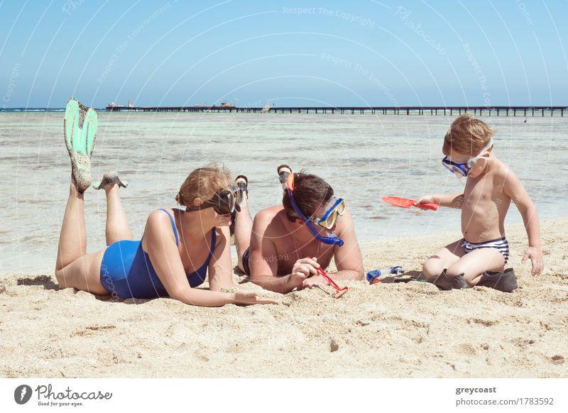 Mutter, Vater und kleiner Sohn im Sommerurlaub am Meer, Sie tragen Schnorchel und Flossen beim Liegen und Spielen am Strand Freude Ferien & Urlaub & Reisen Kind