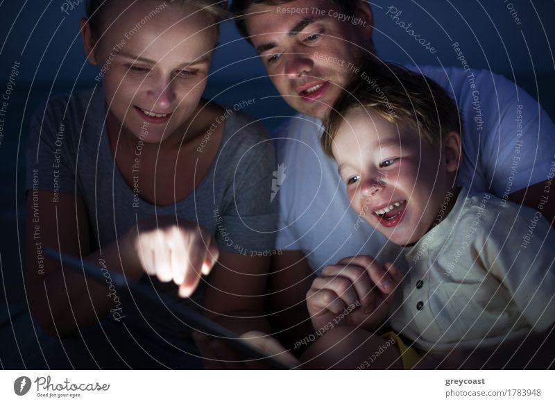 Glückliche dreiköpfige Familie mit Pad spät am Abend. Lachendes Kind schaut auf den Bildschirm, wo die Mutter auf etwas zeigt Freude Freizeit & Hobby Spielen