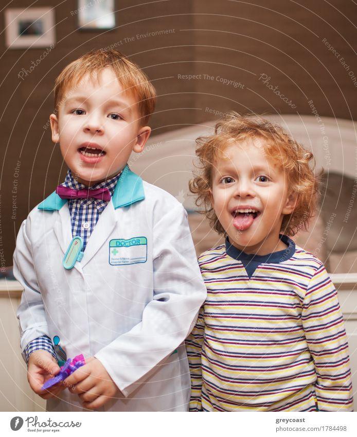 Zwei kleine Jungen als Arzt und Patient. Arzt ist im Laborkittel, ein anderes Kind zeigt die Zunge beim Lächeln Gesundheitswesen Spielen Krankenhaus blond