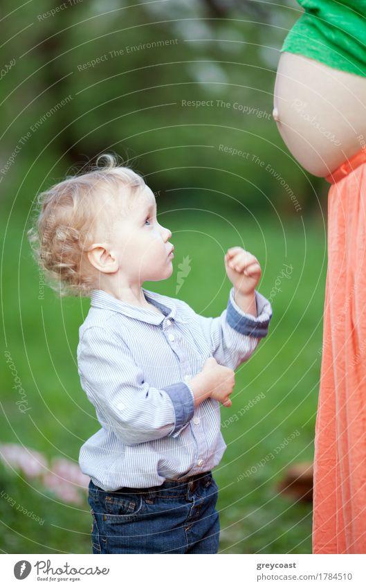 Lovely kleiner Junge Blick auf schwangere Mütter Bauch im Freien. Er erwartet, Bruder oder Schwester zu haben Sommer Kind Frau Erwachsene Mutter