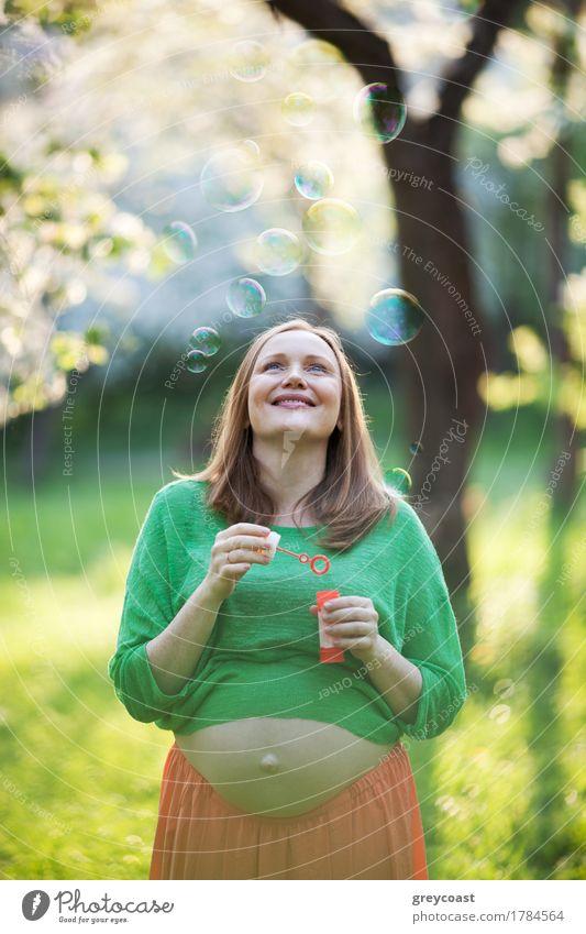 Glückliche schwangere Frau und Luftblasen im Freien Mensch Natur Sommer grün Erholung Freude Mädchen Erwachsene Familie & Verwandtschaft Park Freizeit & Hobby