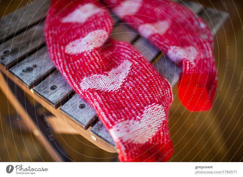 Rote Socken mit Herzmuster auf Holzstuhl Möbel Stuhl Frau Erwachsene Wärme Bekleidung Schuhe Liebe hell niedlich rot Mut Romantik gestrickt Kniestrümpfe Paar