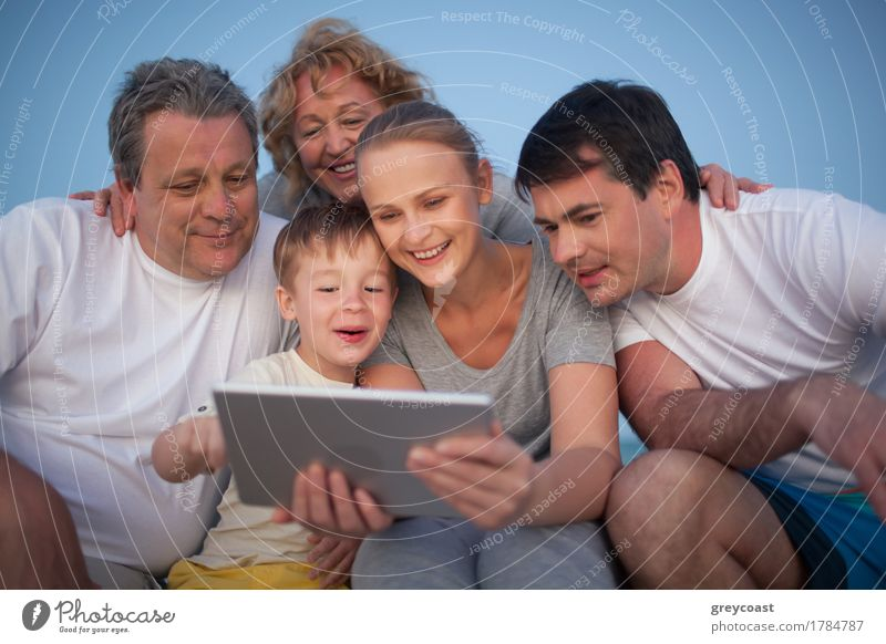 Glückliche große Familie mit guter Zeit zusammen. Großeltern und Eltern Blick auf das Pad Bildschirm während Junge mit ihm Freude Freizeit & Hobby Spielen
