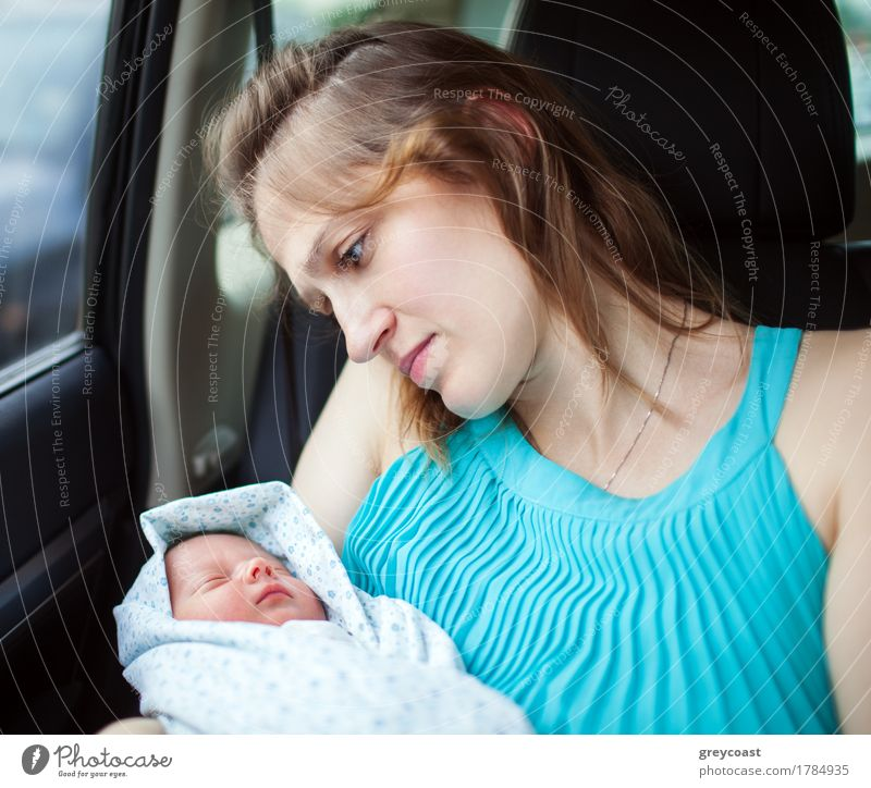 Frau, die das neugeborene Baby sitzt im Auto anhält Kind Jugendliche Hand 18-30 Jahre Erwachsene Liebe Gefühle Familie & Verwandtschaft Verkehr PKW sitzen Arme