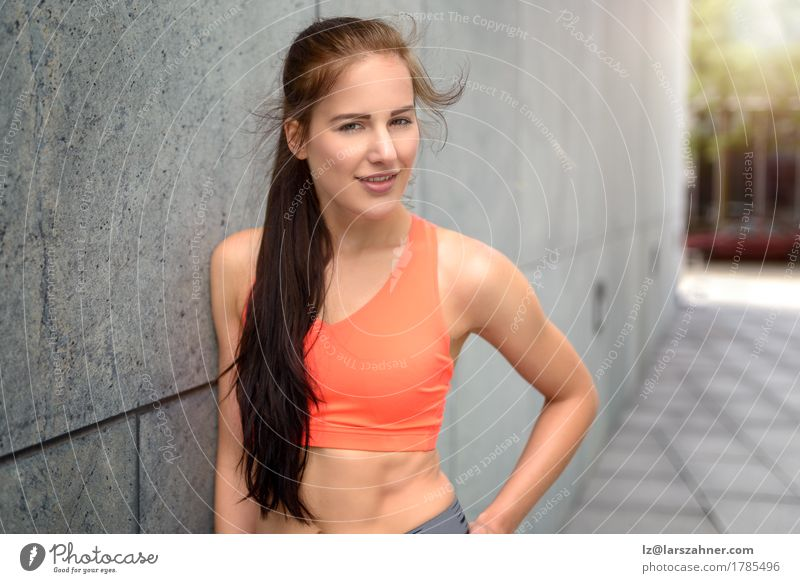 Attraktive sportliche junge Frau, die auf einer Wand sich lehnt Lifestyle Glück Haut Gesicht Sommer feminin Erwachsene 1 Mensch 18-30 Jahre Jugendliche Wind