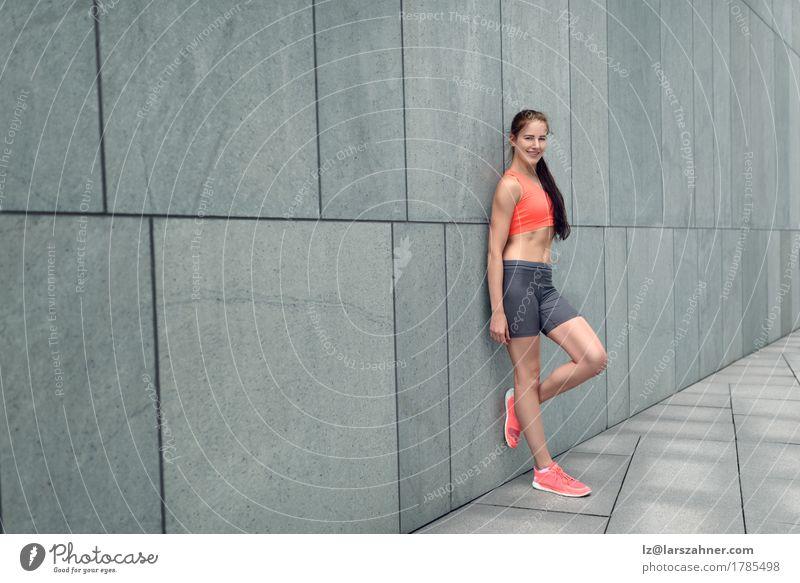 Attraktive sportliche junge Frau, die auf einer Wand sich lehnt Lifestyle Glück Haut Sommer Erwachsene 1 Mensch 18-30 Jahre Jugendliche brünett Lächeln stehen