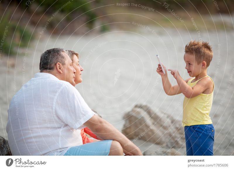 Junge, der das Telefonfoto von den Großeltern im Freien nimmt Mensch Frau Kind Mann Sommer Strand Erwachsene Familie & Verwandtschaft klein Glück Sand