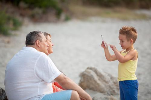 Junge, der das Telefonfoto von den Großeltern im Freien nimmt Glück Sommer Strand Kind PDA Fotokamera Mensch Frau Erwachsene Mann Großvater Großmutter