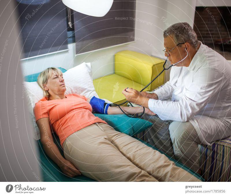 Messender Blutdruck Doktors der Frau zu Hause Mensch Mann Erwachsene Lampe Gesundheitswesen Wohnung blond 45-60 Jahre Krankheit Medikament Sofa Arzt brünett